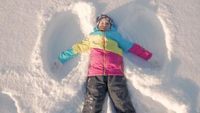 Happy girl lying on a snow and shows angel. A pretty girl in a coat lies on the snow, spreading her arms. Happy girl lying on a snow and shows angel. A pretty stock video footage