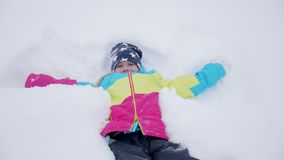 Happy girl lying on a snow and shows angel. A pretty girl in a coat lies on the snow, spreading her arms. Happy girl lying on a snow and shows angel. A pretty stock footage