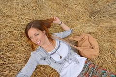 Happy girl lying on a straw pile Royalty Free Stock Photography