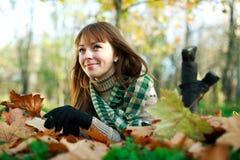 Happy girl lying on yellow leaves Royalty Free Stock Image