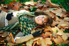 Happy girl lying on yellow leaves outdoors Royalty Free Stock Images