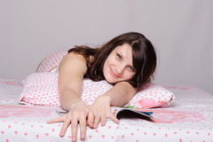 Happy girl with a magazine in bed Royalty Free Stock Image