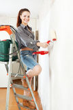 Happy girl makes repairs  at home Stock Photo