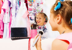 Happy girl makes up with brush looking in mirror Stock Photography