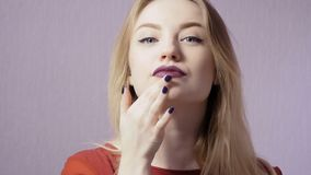 Happy girl with makeup and purple lips at the violet background. Young beautiful woman is in the bright studio. Young pretty makeup woman looks in camera and stock video