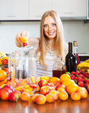 Happy girl making beverages with fruits Royalty Free Stock Images