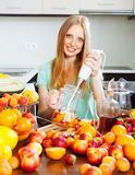 Happy girl making fruits cocktail with blender Royalty Free Stock Image