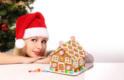 Happy Girl making Gingerbread House. Young Woman with Santa Hat Royalty Free Stock Photos