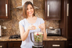 Happy girl making a healthy juice Stock Images
