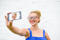 Happy girl making selfie with smartphone on white. Portrait of happy blond girl making selfie with smartphone. Young woman wearing funny hipster glasses smiling Stock Image
