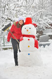 Happy girl making a snowman Stock Image