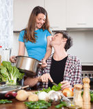 Happy girl and the man cooking food Stock Photography