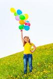 Happy girl with many flying balloons in the air Stock Images
