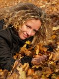Happy girl in maple leaves Stock Image