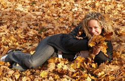 Happy girl in maple leaves Stock Photo