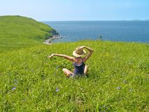 Happy girl on the meadow against the sea Stock Photography