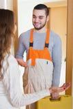 Happy girl meeting workman. Housewife meeting smiling workman at apartment doorway Stock Photography