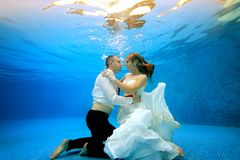 Happy girl and man in wedding dresses underwater hugging the bottom of the pool and looking at each other. Happy girl and men in wedding dresses underwater Royalty Free Stock Photo