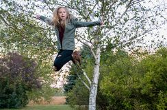Happy girl in midair jump. Happy young Caucasian girl in midair with rural scenic background royalty free stock photos