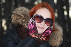 Happy girl in mittens and sunglasses in forest Stock Photos