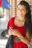Happy girl with mobile phone. A happy hispanic student holding her mobile phone outdoors Royalty Free Stock Images