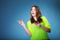 Happy girl with mobile phone pointing copyspace Royalty Free Stock Images