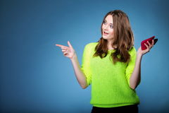 Happy girl with mobile phone pointing copyspace Stock Photo