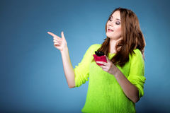 Happy girl with mobile phone pointing. Happy girl with mobile phone in pink cover pointing her finger blue background Royalty Free Stock Photos