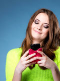 Happy girl with mobile phone reads message Royalty Free Stock Image