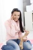 Happy girl on mobile sitting between heels Stock Image