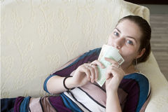 Happy girl with money in hands. Beautiful young girl laying on couch and holding euro Stock Images