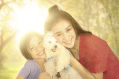 Happy girl and mother with dog at the park Royalty Free Stock Photos