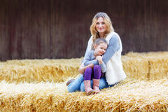 Happy girl and mother having fun with hay on a farm Stock Image