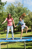 Happy girl and mother jumping high on trampoline in park Stock Photo