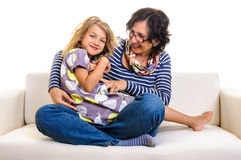 Happy girl and mother playing on sofa Royalty Free Stock Photography
