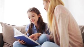 Happy girl with mother reading book at home stock footage