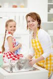 Happy girl and mother washing dishes Royalty Free Stock Photos