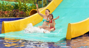 Girl and mother  on water slide Stock Images