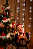 Happy girl near Christmas tree with present Stock Photography