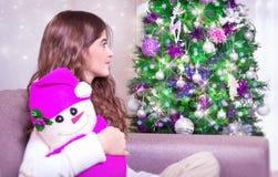 Happy girl near Christmas tree Stock Photos