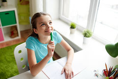 Happy girl with notebook dreaming at home Stock Photo