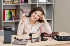 Happy girl in the office with cosmetics. Young woman sitting at office table, laid out on the table cosmetics Stock Photos
