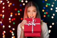 Happy girl opening Christmas box which is glowing inside. Christmas Gift Stock Photo