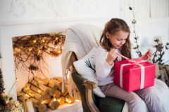 Happy girl opening Christmas gifts by a decorated fireplace in cozy light living room on Xmas eve Royalty Free Stock Image