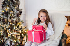 Happy girl opening Christmas gifts by a decorated fireplace in cozy light living room on Xmas eve Royalty Free Stock Photography