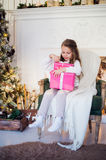 Happy girl opening Christmas gifts by a decorated fireplace in cozy light living room on Xmas eve Stock Photo