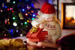 Happy girl opening Christmas gifts by a fireplace stock photos