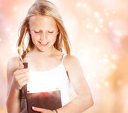 Happy Girl Opening a Present. Happy Blonde Girl Opening a Present Royalty Free Stock Images