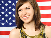 Happy girl opposite an American flag Royalty Free Stock Images