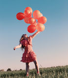 Happy girl with orange balloons Royalty Free Stock Image